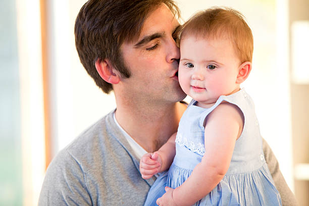 Father kissing his baby daughter on the cheek Father kissing his baby daughter on the cheek little girl kissing dad on cheek stock pictures, royalty-free photos & images