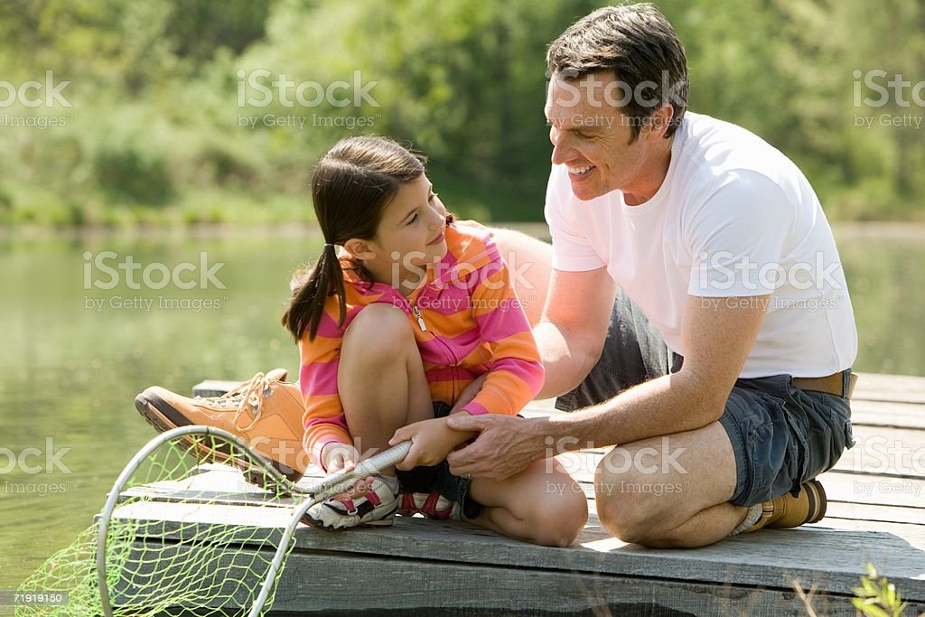 Father kneeling next to daughter on jetty, holding fishing net royalty-free stock photo