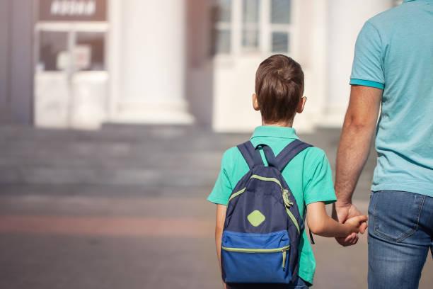 padre lleva un niño en la escuela infantil van de la mano. padre e hijo con mochila a la espalda. - regreso a clases fotografías e imágenes de stock