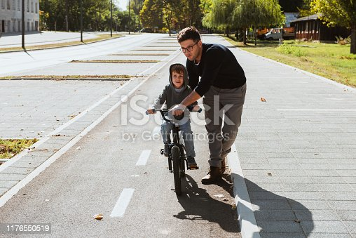 860036242 istock photo Father Learning his son to ride a bicycle 1176550519