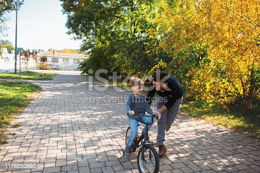 860036242 istock photo Father Learning his son to ride a bicycle 1176550992