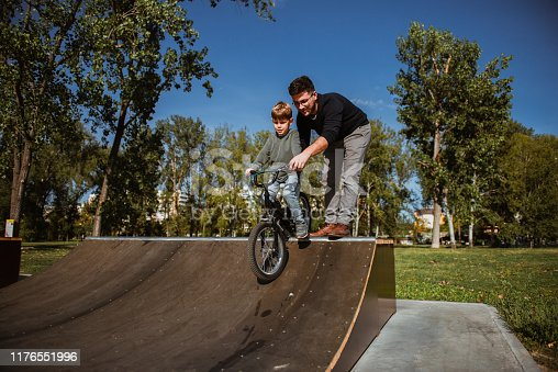 860036242 istock photo Father Learning his son to ride a bicycle 1176551996