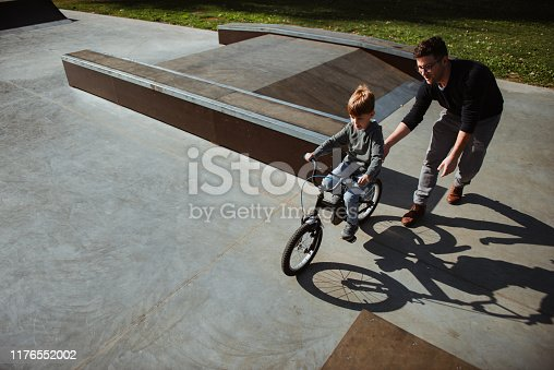 860036242 istock photo Father Learning his son to ride a bicycle 1176552002