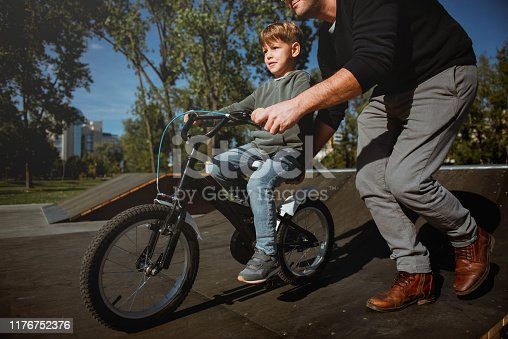 860036242 istock photo Father Learning his son to ride a bicycle 1176752376