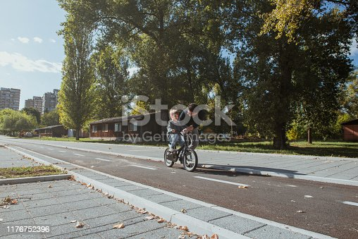 860036242 istock photo Father Learning his son to ride a bicycle 1176752396