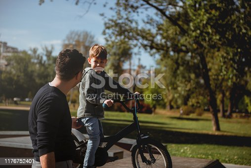 860036242 istock photo Father Learning his son to ride a bicycle 1176752401