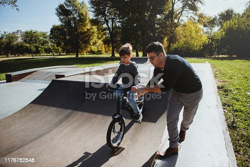 860038590 istock photo Father Learning his son to ride a bicycle 1176752548