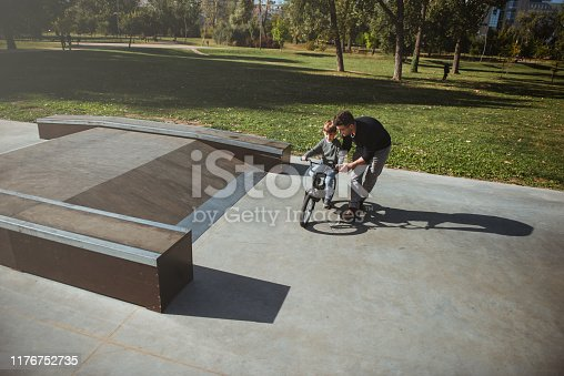860036242 istock photo Father Learning his son to ride a bicycle 1176752735