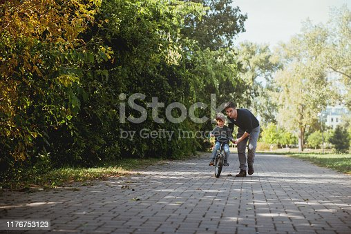 860036242 istock photo Father Learning his son to ride a bicycle 1176753123