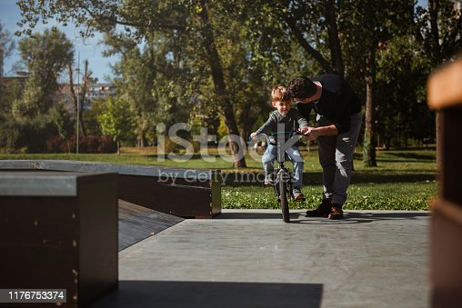 860036242 istock photo Father Learning his son to ride a bicycle 1176753374