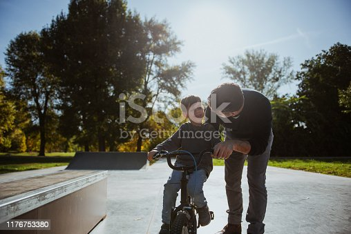 860038590 istock photo Father Learning his son to ride a bicycle 1176753380