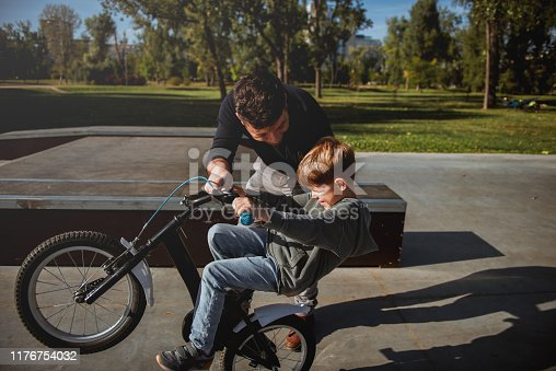 istock Father Learning his son to ride a bicycle 1176754032