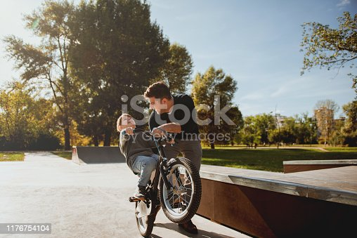860036242 istock photo Father Learning his son to ride a bicycle 1176754104