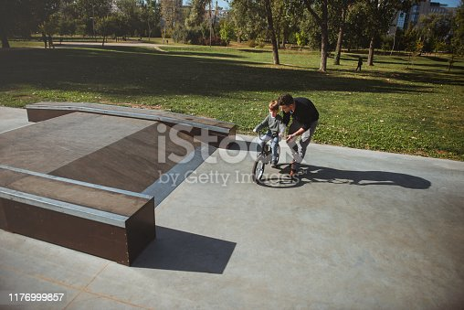 860036242 istock photo Father Learning his son to ride a bicycle 1176999857