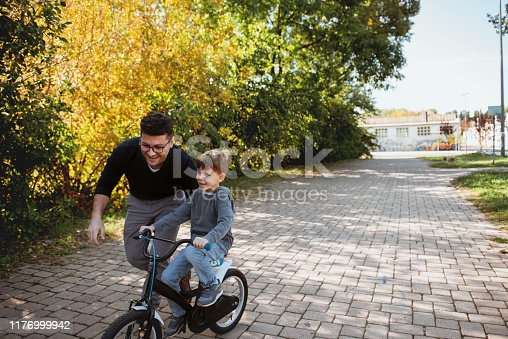 860036242 istock photo Father Learning his son to ride a bicycle 1176999942