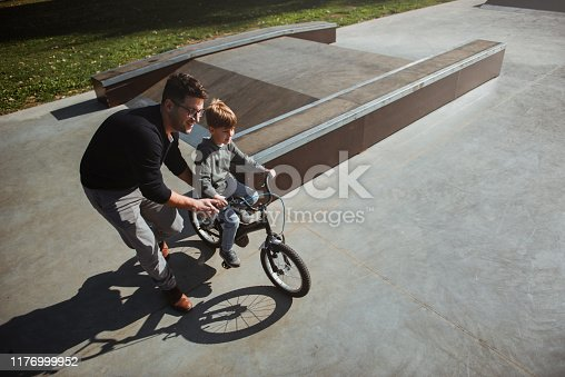 860036242 istock photo Father Learning his son to ride a bicycle 1176999952