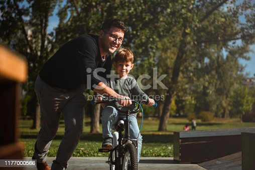 860036242 istock photo Father Learning his son to ride a bicycle 1177000566