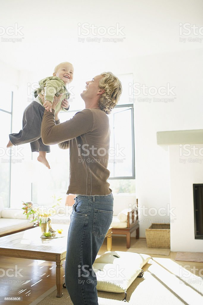 Father lifting baby son in air royalty-free stock photo