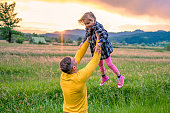 Smiling father lifting his daughter into the air on a meadow at sunset.