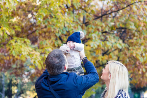 Father lifting his son in the park with his wife stock photo
