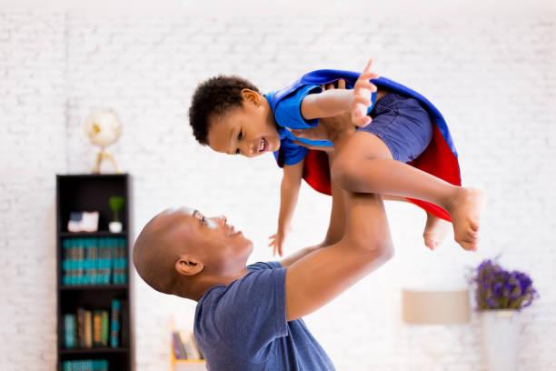 father lifting son up with super hero costume at home - baby super hero imagens e fotografias de stock