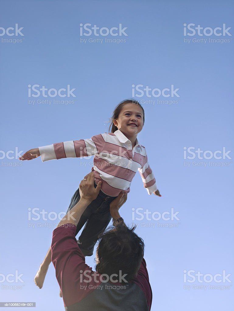 Father lifting up daughter (6-7), low angle view against sky royalty-free stock photo