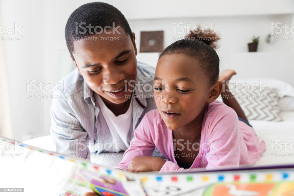 Father listening to his daughter read. stock photo