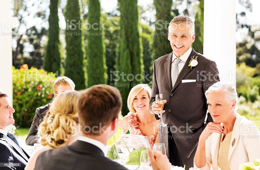 Father Looking At Couple While Giving Speech During Reception stock photo