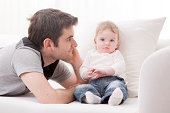 Father looking at her beautiful daughter on the sofa