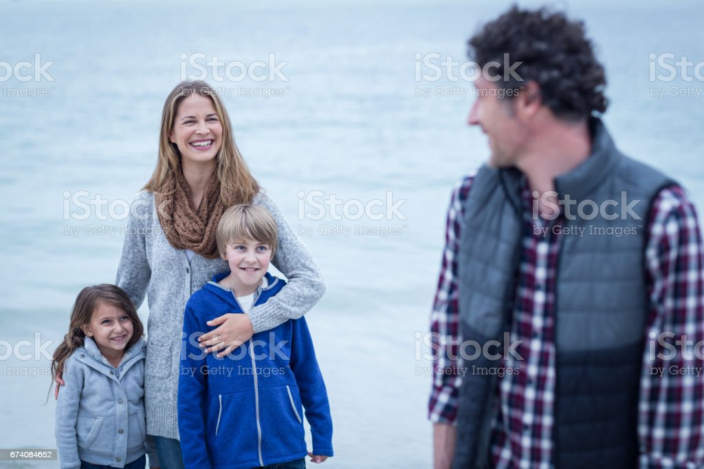 Father looking at mother and children on beach royalty-free stock photo