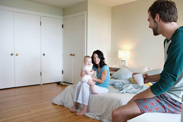 vater blick in die mutter mit baby mädchen (9 – 12 monate - mutterkleiderschrank stock-fotos und bilder
