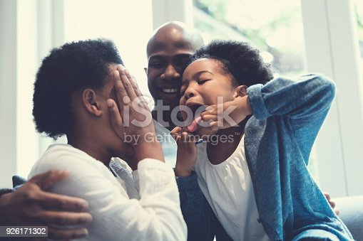 istock Father looking at playful daughters on sofa 926171302
