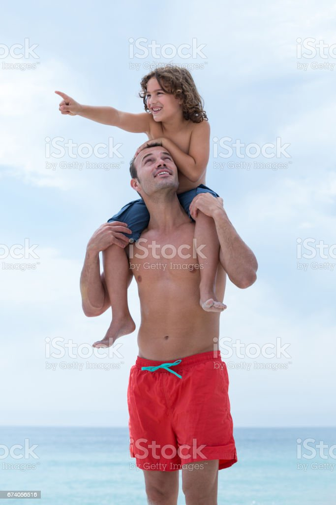 Father looking at son while carrying him on beach royalty-free stock photo