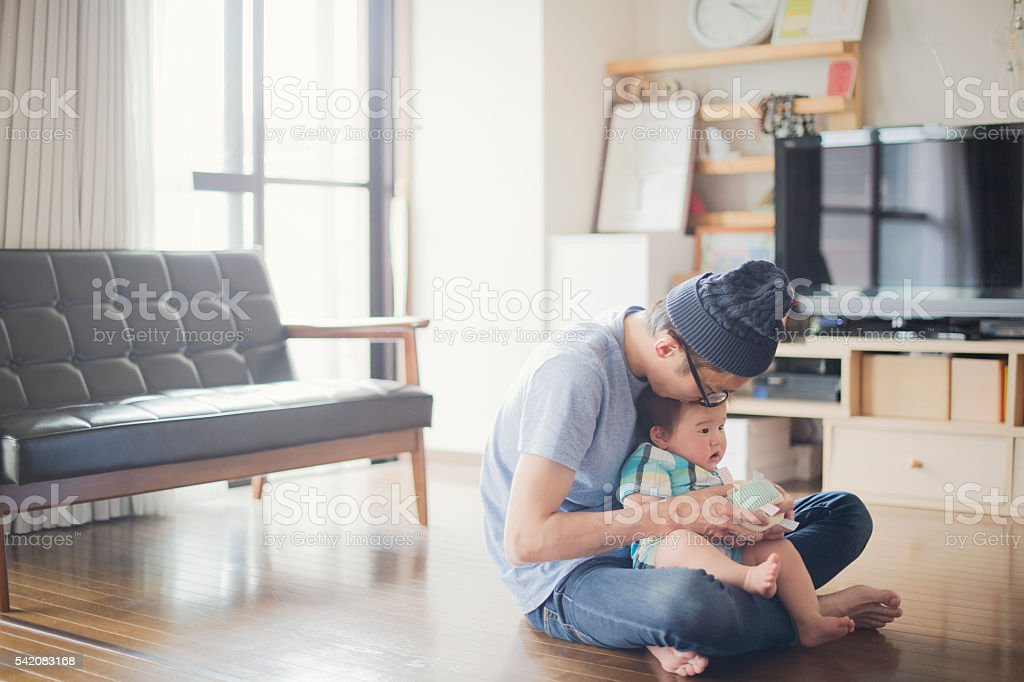 Father loving his baby boy at home. stock photo