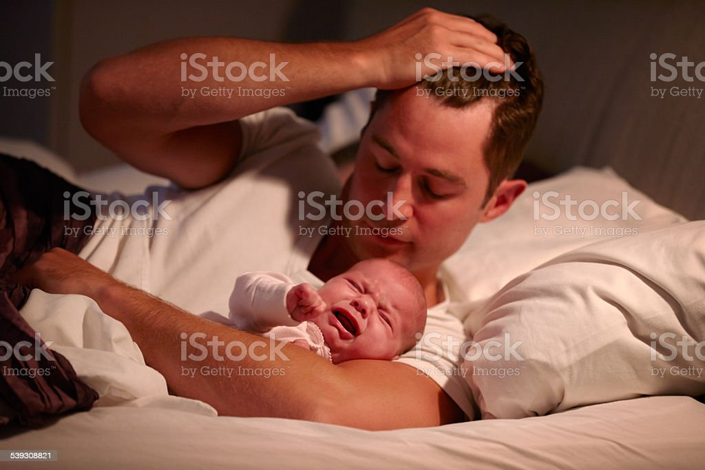 Father Lying In Bed With Crying Baby Daughter stock photo