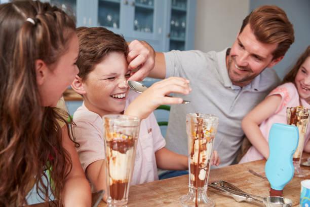 father making ice cream sundaes with children at home - coppa gelato foto e immagini stock