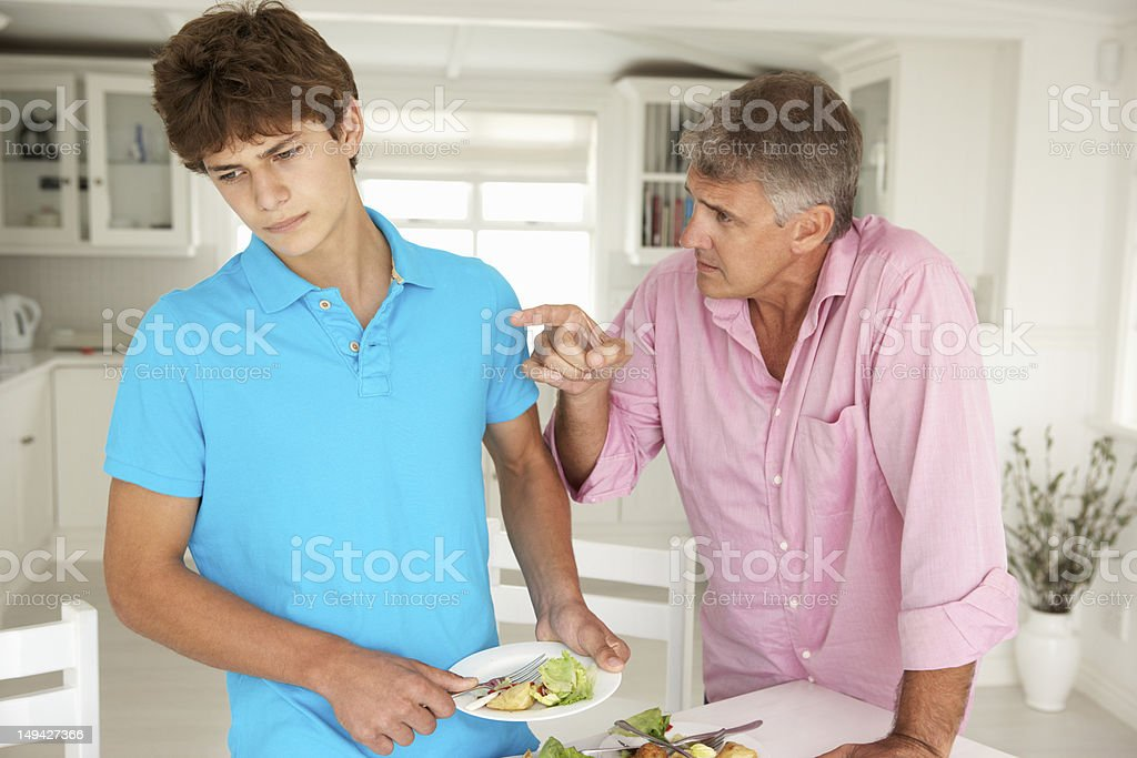 Father making teenage son do housework stock photo