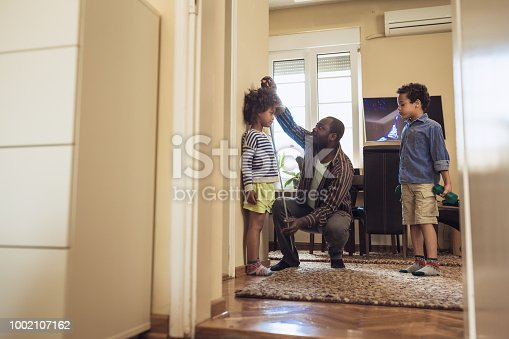 Shot of a father measuring daughter height against a wall at home