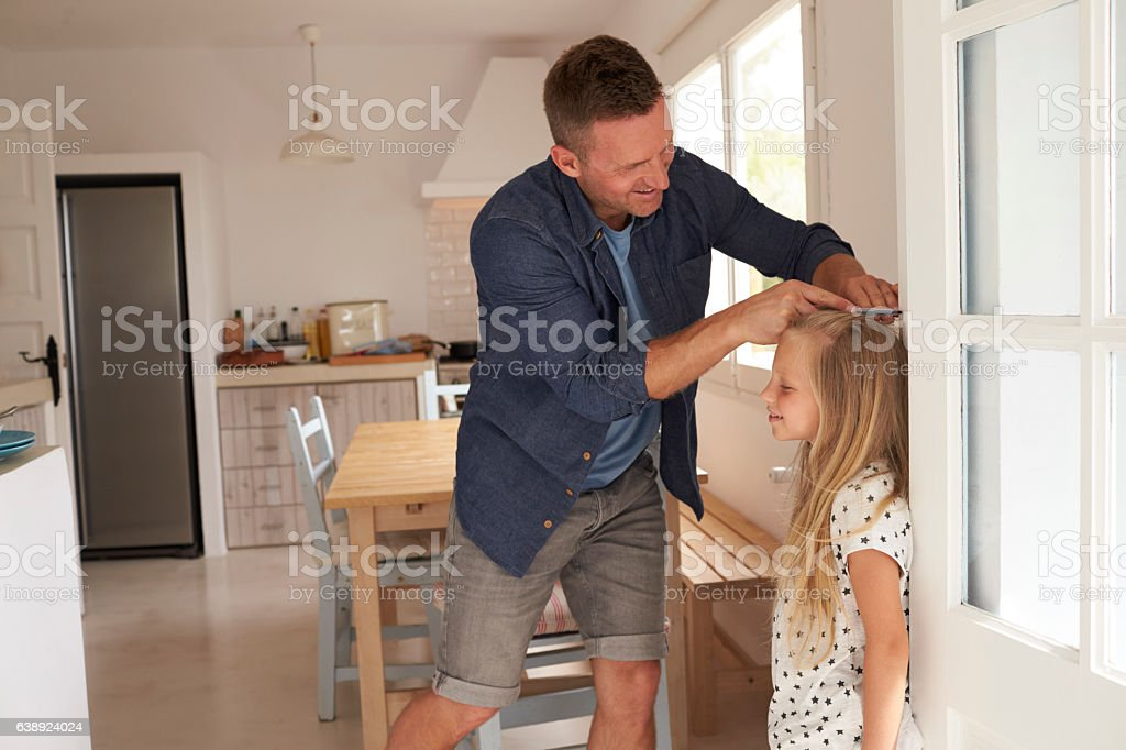 Father Measuring Daughter's Height Against Wall stock photo