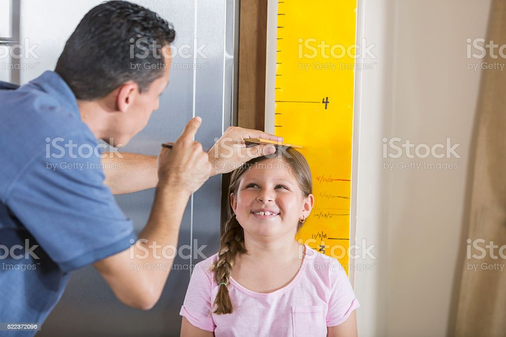 Father measuring girl's height on growth chart stock photo