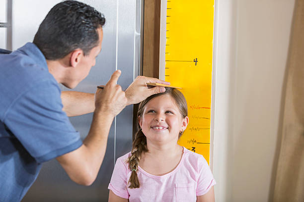 father measuring girl's height on growth chart - height measurement stock photos and pictures