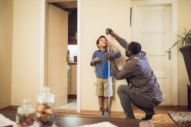 father measuring sons height - height measurement stock photos and pictures