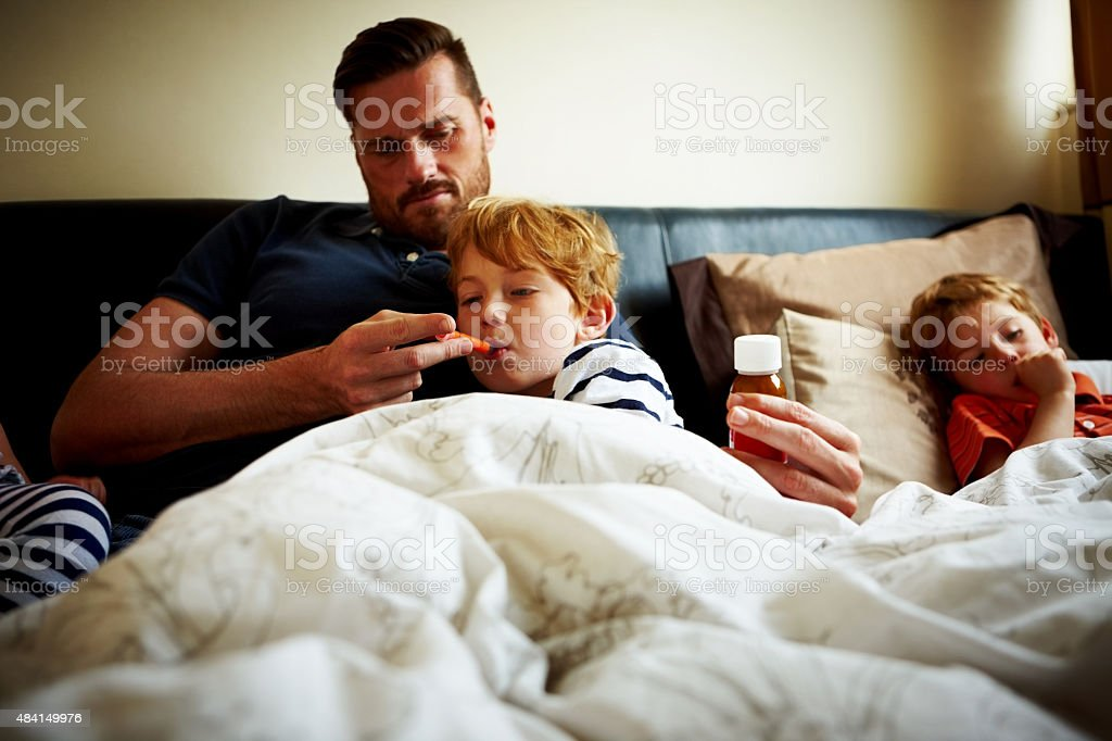 Father measuring temperature of his sick son stock photo