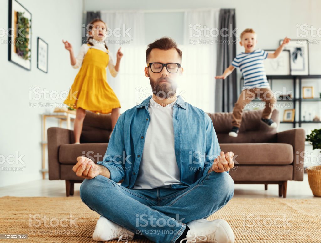 Father meditating in room with playful kids Tranquil young man in casual wear sitting on floor in lotus position and meditating while kids having fun and jumping on sofa at home Adult Stock Photo