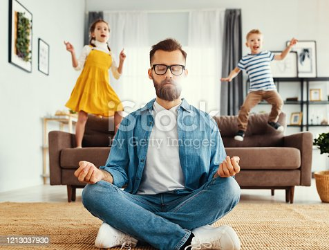 Tranquil young man in casual wear sitting on floor in lotus position and meditating while kids having fun and jumping on sofa at home
