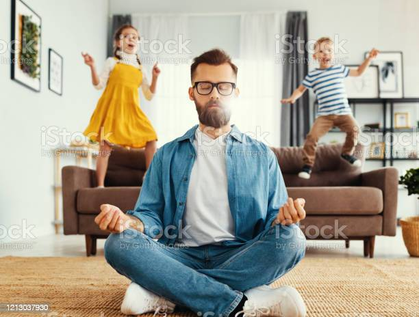 Father Meditating In Room With Playful Kids Stock Photo - Download Image Now