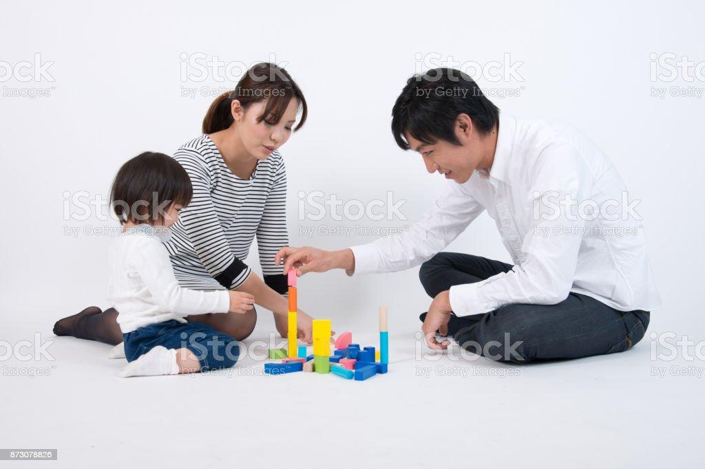 父、母、白い背景の上のビルディング ブロックと一緒に遊ぶ子 ストックフォト