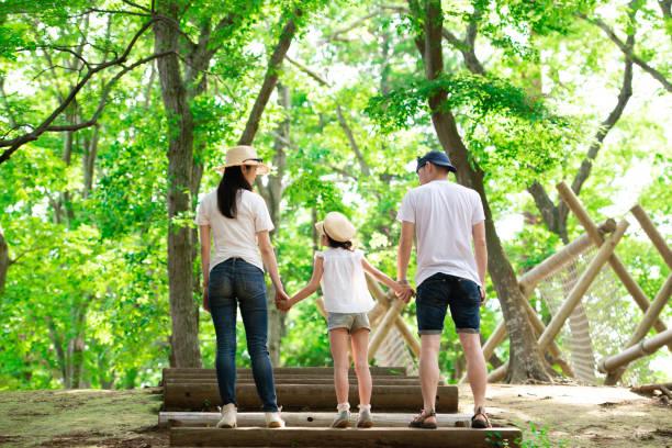 森の公園で手をつないでいる父、母、娘 - シンプルな暮らし ストックフォトと画像