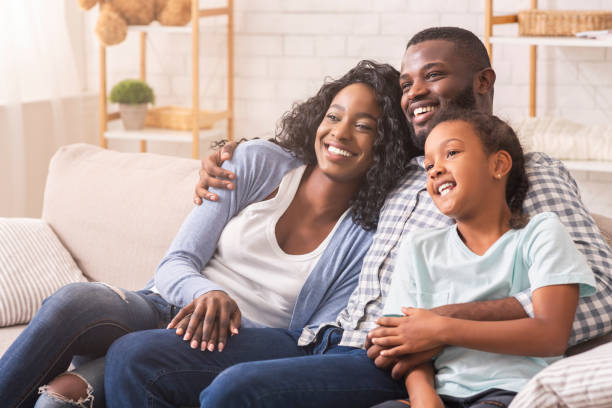 Vater, Mutter und Tochter schauen gemeinsam vor dem Fernseher, entspannen zu Hause – Foto