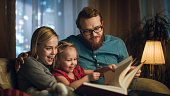 Father, Mother and Little Daughter Reading Children's Book on a Sofa in the Living Room. It's Evening.